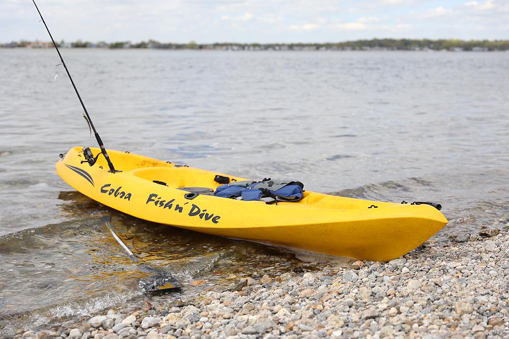 A bright blue kayak on the beach.